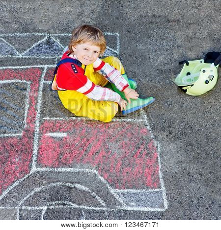 Creative leisure for kids: adorable child of four years having fun with fire truck picture drawing with chalk, outdoors. Dreaming of future profession.