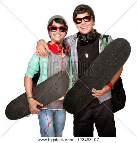 Two happy skateboarders listening music in headphones wearing trendy urban clothes and sunglasses isolated on white background, active modern life of youth