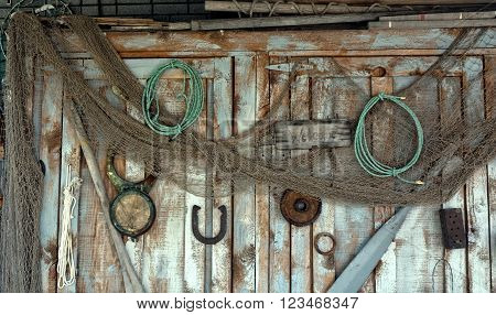 Forgotten equipment hangs rusting on a weather worn shed door.