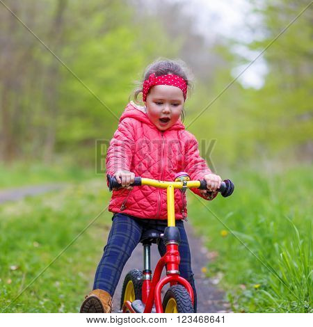Happy funny kid girl and colorful raincoat riding his first bike on summer day. Active leisure for children outdoors.