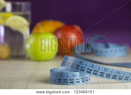 dietic ration for weight loss with organic fresh fruits and lemon drink with blue measure tape in front