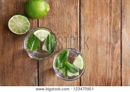 Fresh cocktails with mint, ice and lime on wooden table background, view from above