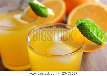 Two orange juices with ice and orange on, closeup