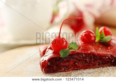 Cherry strudel with mint on cutting board