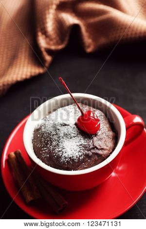 Chocolate cake in a red mug with a cherry on a wooden background, close up