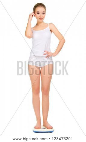 Young surprised girl on scales isolated