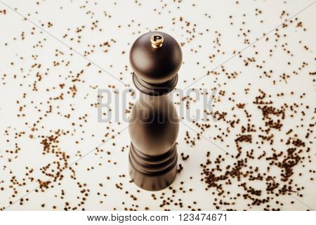 pepper mill and peppercorns, white background