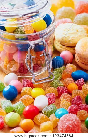 Colorful candies, macaroon and jujube in jar on the wooden table