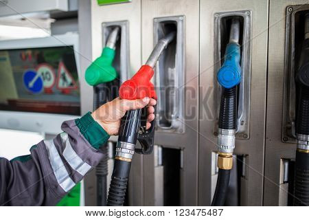 Closeup of male hand holding gas pump nozzle at gas station.