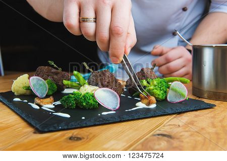 Professional chef decorate plate with meat greens. Man prepares delicious meals in kitchen. Chunks of roasted meat on  black plate with greens, radish, broccoli, asparagus and sauce. Close-up. Tweezers in  hand
