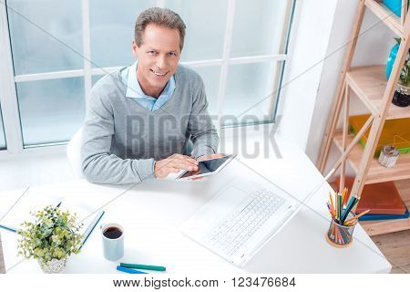 Top view photo of stylish adult businessman while working day in office. Businessman with laptop and tablet computer, looking at camera and smiling. Office interior with bookcase and big window