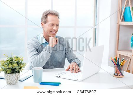 Stylish adult businessman while working day in office. Businessman using laptop, looking at camera and smiling. Office interior with bookcase and big window