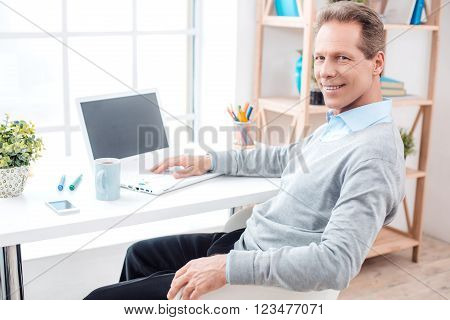 Stylish adult businessman while working day in office. Businessman with laptop, looking at camera and smiling. Office interior with big window and bookcase