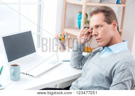 Stylish adult businessman while working day in office. Businessman with laptop and glasses. Office interior with big window and bookcase