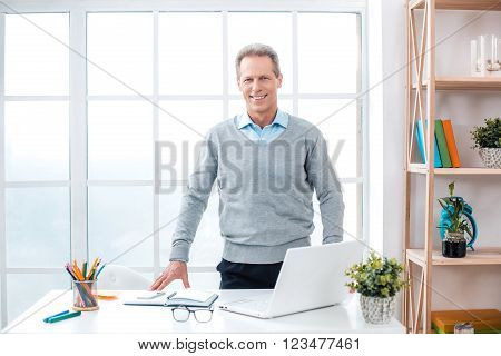 Stylish adult businessman while working day in office. Businessman with laptop looking at camera and smiling. Office interior with big window and bookcase