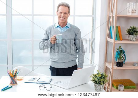 Stylish adult businessman while working day in office. Businessman with laptop, drinking coffee, looking at camera and smiling. Office interior with big window and bookcase