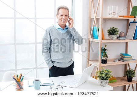 Stylish adult businessman while working day in office. Businessman using mobile phone, looking at camera and smiling. Office interior with big window and bookcase