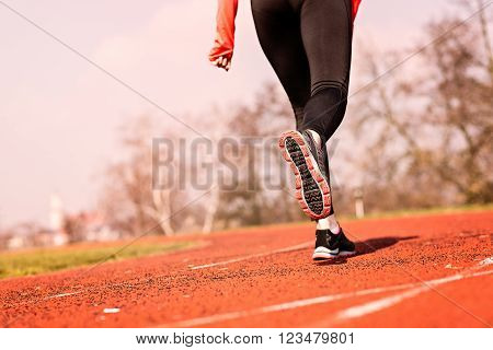 Woman Running Around The Track On A Sunny Spring Day.