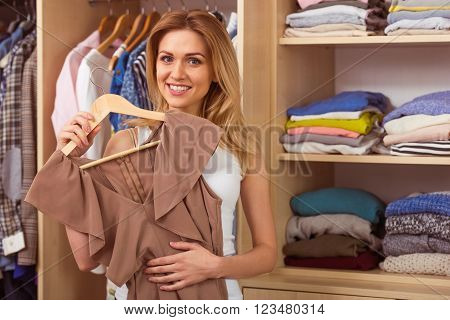 Beautiful girl is smiling and looking at camera while choosing a dress in her dressing room
