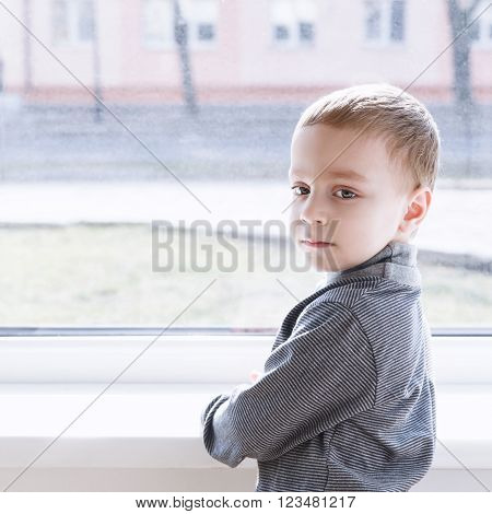small boy standing near window and thinking about something
