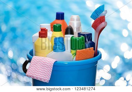 Detergents in color bottles brush and napkins in a bucket against a blurred seawater.