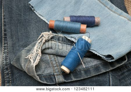 Sewing supplies and old clothes for repair. Photo