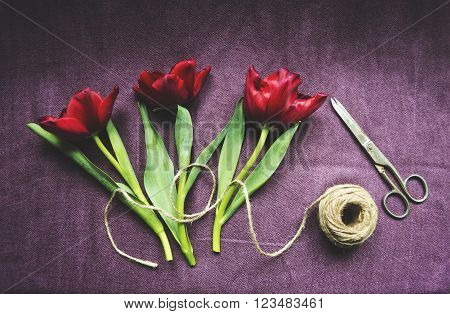 Three red tulips, twine and scissors. Top view