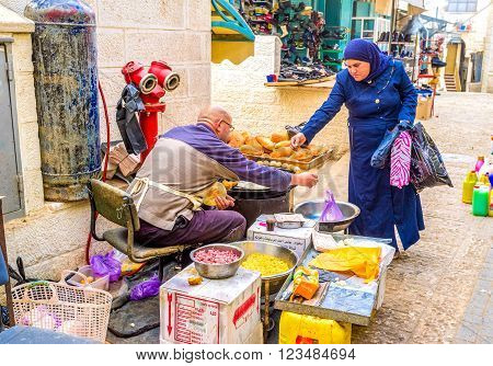 BETHLEHEM PALESTINE - FEBRUARY 18 2016: The woman buying falafel - traditional street food in Palestine on February 18 in Bethlehem.