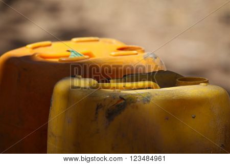 Empty water cans at a well in Africa. ** Note: Shallow depth of field