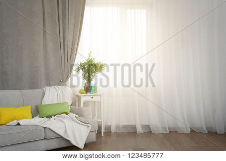 Grey sofa and small table with green plant on curtain background