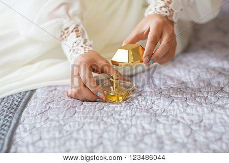 bride applying gentle perfume on her wrist. Bride reveals favorite perfume.
