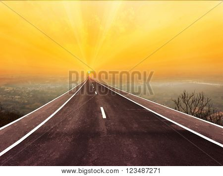 Long paveway road aboved blurred top city view along to golden sun rise for abstract background with copy space