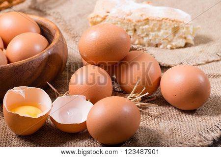 Eggs and pie on a sacking. One egg is broken rural style a close up