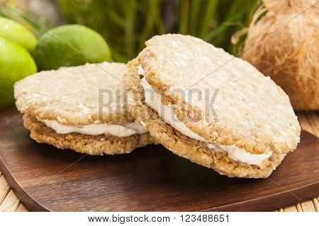 Vegan oatmeal cookie ice cream sandwich with coconut lime ice cream outdoors
