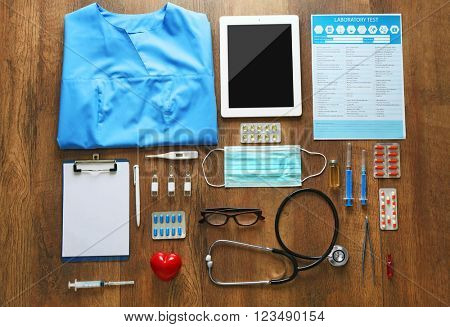 Doctor table with medical items, medicines and laptop, top view