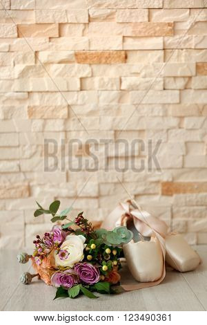 Bouquet of roses and ballet shoes on brick wall background