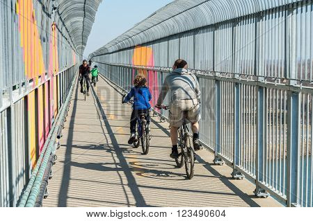 Montreal, Canada - March 27th 2016. Group Of Cyclists on Jacques Cartier Bridge multicolored passageway.