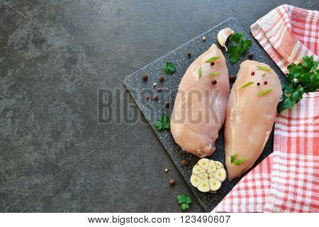 Fresh raw chicken breast on a black background