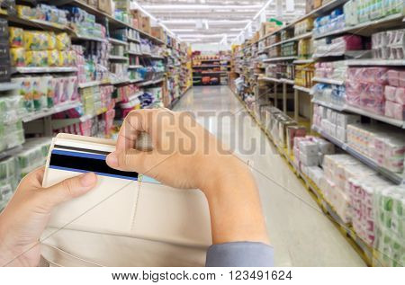 Isolated business women hands pull credit card out of wallet with shopping mall blurred background and copy space