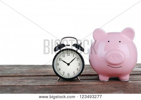 Pink piggy bank and clock on white background