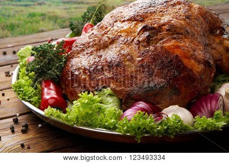 Restaurant food, roasted pork shoulder. Meat dish. Festive banquet dish, holiday dish. Catering. Served main dish, roasted pork with vegetables and herbs. Closeup at wooden rustic background.