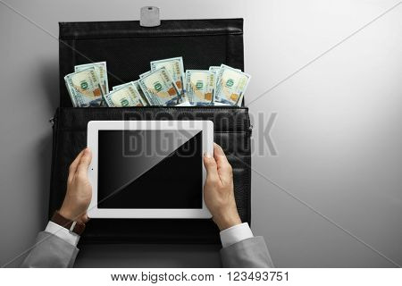 Businessman with tablet and brief case full of money money