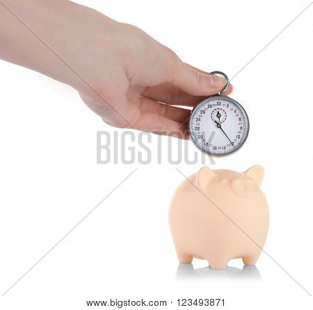 Beige piggy bank and a hand holding timer above it isolated on white