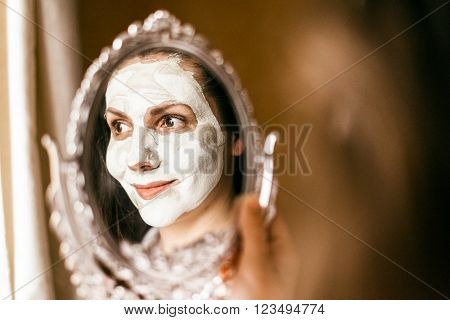 Woman applying mask of clay skin on face looking in mirror. Woman applying mask of clay skin on face looking in mirror.