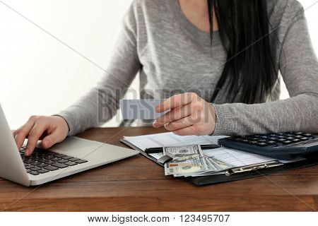 Dark-haired woman set aside calculator, money, paper and using computer on the wooden table to pay the bills, close up