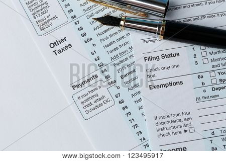 1040 Individual Income Tax Return Form for 2015 year with a pen to fill on the white desk, close up