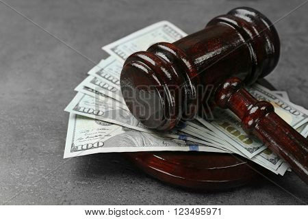 Law gavel with dollars on grey background, closeup