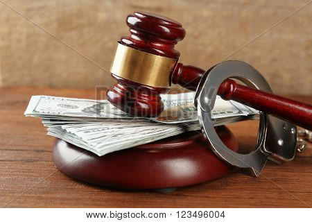 Law gavel with dollars and handcuffs on wooden table background, closeup