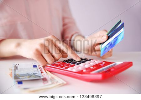 Female calculate with credit card and euro money, closeup