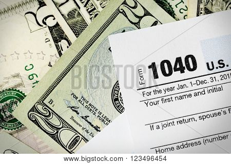 1040 Individual Income Tax Return Form with twenty dollar bills, close up